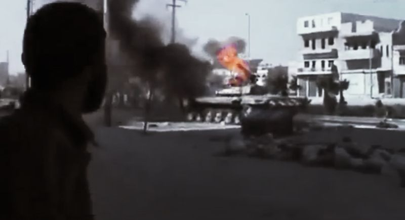 **FILE** In this image made from amateur video released by the Ugarit News and accessed July 23, 2012, a Free Syrian Army soldier looks at a military tank caught on fire during clashes with Syrian government troops in Aleppo, Syria. (Associated Press/Ugarit News via AP video)