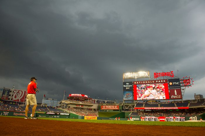 **FILE ** Assistant groundskeeper Mike Hrivnak keeps an eye on the approaching storm Aug. 20, 2012, during a rain delay in Washington, D.C. (Rod Lamkey Jr./The Washington Times)