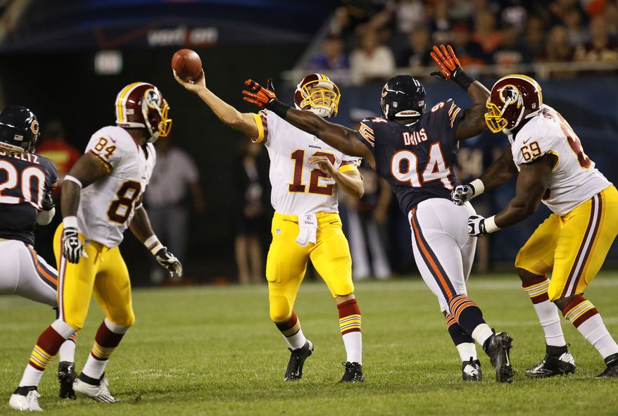 Washington Redskins quarterback Kirk Cousins (12) passes under pressure from Chicago Bears defensive end Chauncey Davis (94) in the second half of an NFL preseason football game in Chicago, Saturday, Aug. 18, 2012. (AP Photo/Charles Rex Arbogast)