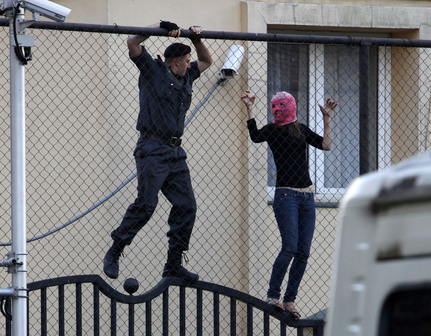 A policeman tries to detain a masked supporter of the Russian punk group Pussy Riot inside the Turkish embassy near the court in Moscow on Aug. 17, 2012. A Moscow judge sentenced each of three members of the band to two years in prison on hooliganism charges following a trial that has drawn international outrage as an emblem of Russia's intolerance to dissent. (Associated Press)