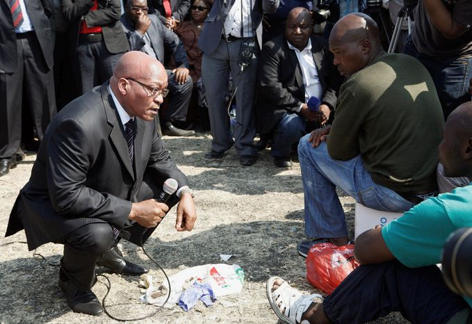 "South Africa's President Jacob Zuma, left, interacts with striking mine workers at the Lonmin mine near Rustenburg, South Africa, Wednesday, Aug. 22, 2012. Demands for higher wages spread to at least two other platinum mines in South Africa and raise fears instability could spread to more of the country's mines that provide 75 percent of the world's supply of the precious metal. South Africa's miningweb.co.za Web site calls it ""a possibly ominous development."" A 12-day strike at the Lonmin PLC mine resulted in police killing 34 striking miners and wounding another 78 last week. (AP Photo/Themba Hadebe)"