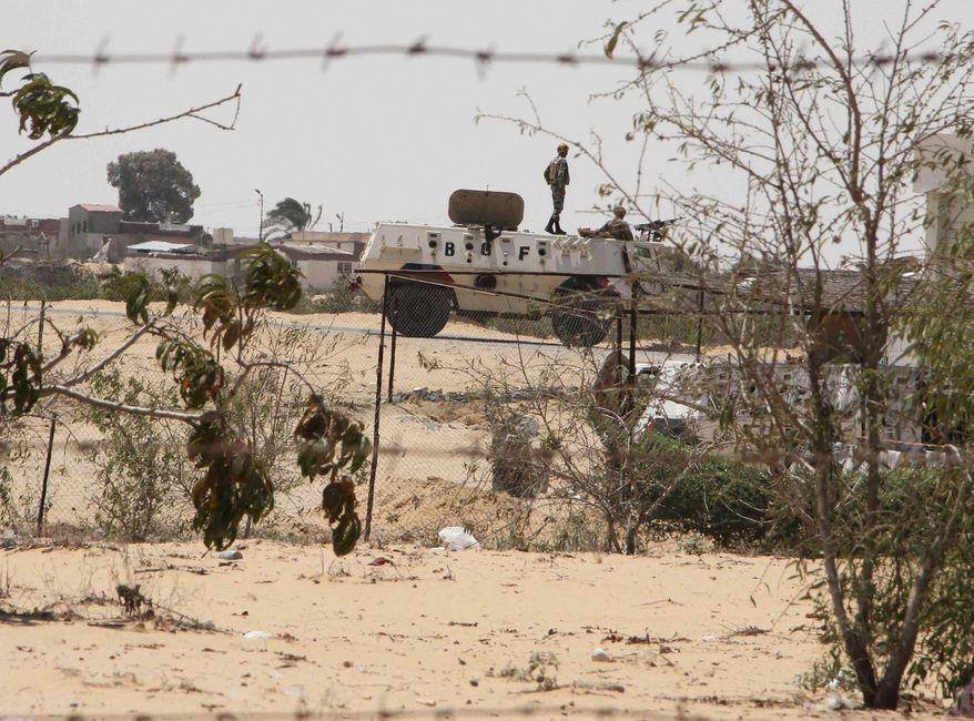 ** FILE ** Egyptian guards patrol near the border with Israel. After decades of neglect and with the collapse of government authority, Egypt's Sinai Peninsula has become fertile ground for Islamic extremists, who are making inroads in the court system. (Associated Press)