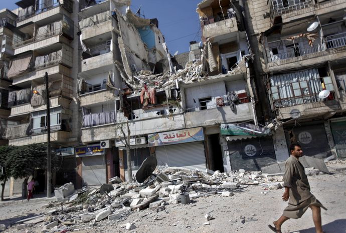 ** FILE ** A Syrian walks by a building destroyed in an airstrike in Aleppo, Syria, on Friday, Aug. 17, 2012. The growing use of air power by the Syrian regime has caused a spike in civilian casualties, activists say. (AP Photo/Khalil Hamra)
