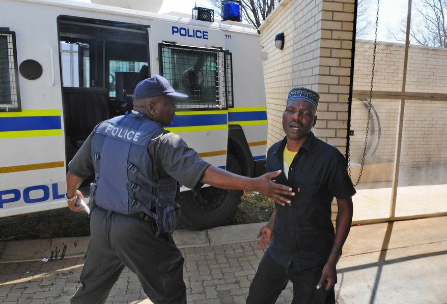 Chris Mahlangu, right, is led away from the court in Ventersdorp, South Africa, Wednesday, Aug. 22, 2012, after receiving a life sentence for the murder of Eugene TerreBlanche. (AP Photo)