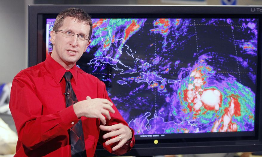 Rick Knabb, director of the National Hurricane Center, updates a reporter on Tropical Storm Isaac on Wednesday, Aug. 22, 2012, in Miami. The agency said Isaac was expected to strengthen and could become a hurricane by Thursday. (AP Photo/Alan Diaz)