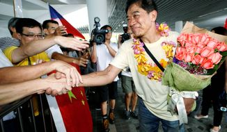 Chinese activist Henry Wong Fahman (center) greets supporters in Hong Kong last month. The activists were part of a group that evaded the Japanese Coast Guard. (Associated Press)