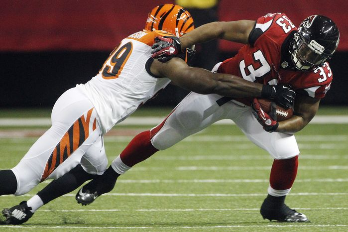 Cincinnati Bengals linebacker Manny Lawson (99) defends against Atlanta Falcons running back Michael Turner (33) during the first half of an NFL preseason football game, Thursday, Aug. 16, 2012, in Atlanta. (AP Photo/John Bazemore)