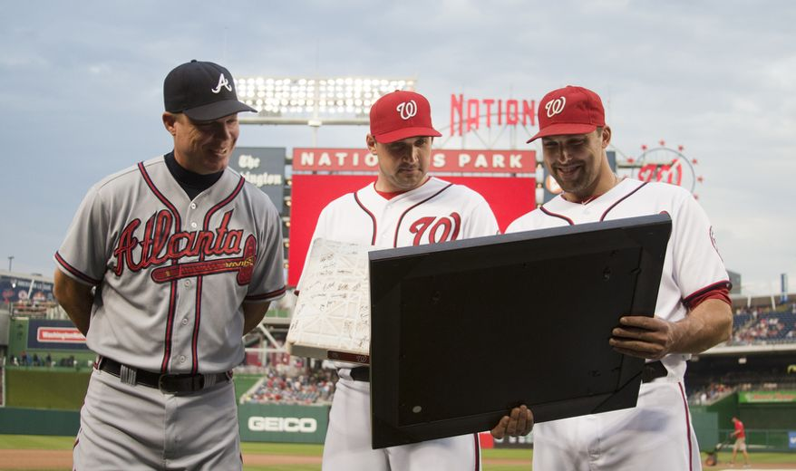 Washington Nationals Mark DeRosa presents a signed photograph of Chipper Jones to him as Ryan Zimmerman (center) looks on Wednesday, Aug. 22, 2012, in Washington, DC. Jones said he would be retiring after this session. He has played his entire 19 year career was an Atlanta Brave, winning one World Series title with them in 1995. (Craig Bisacre/The Washington Times)