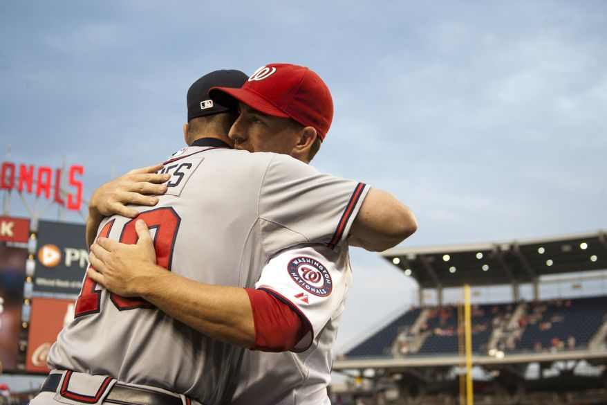 Washington Nationals Adam LaRoche hugs Chipper Jones during a ceremony in his honor Wednesday, Aug. 22, 2012, in Washington, DC. Jones said he would be retiring after this session. He has played his entire 19 year career was an Atlanta Brave, winning one World Series title with them in 1995.  (Craig Bisacre/The Washington Times)