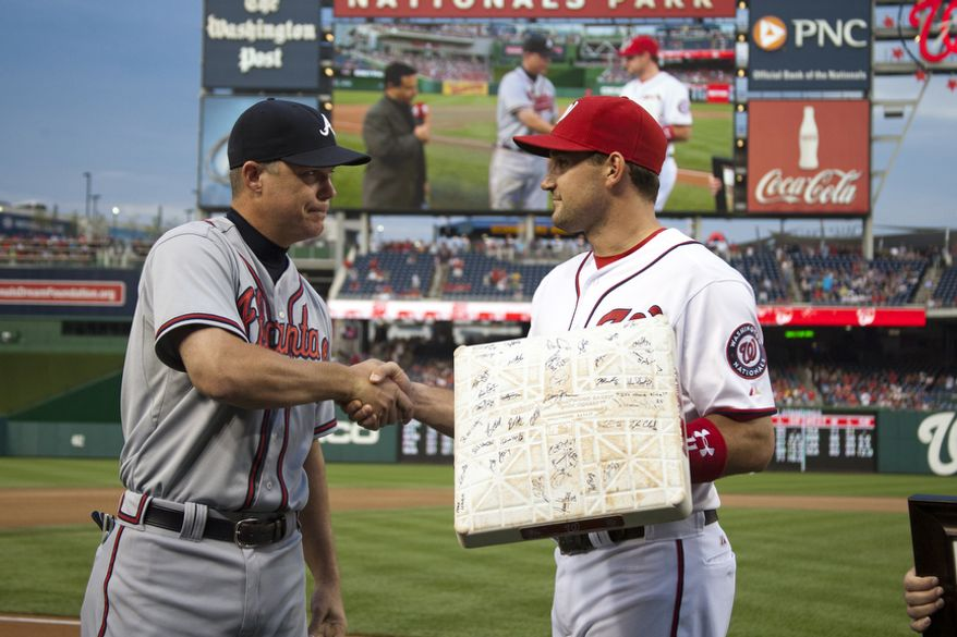 Washington Nationals, Ryan Zimmerman, presents a teamed signed third base to veteran third baseman Chipper Jones, Wednesday, Aug. 22, 2012, in Washington, DC. Jones said he would be retiring after this session. He has played his entire 19 year career was an Atlanta Brave, winning one World Series title with them in 1995. bhp (Craig Bisacre/The Washington Times)