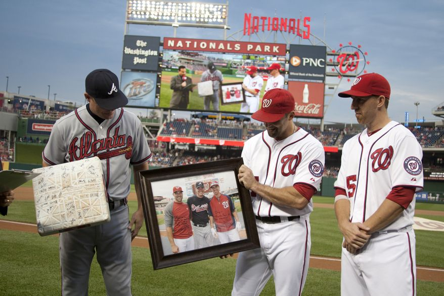 Washington Nationals Mark DeRosa and Adam LaRoche present a signed photograph of him, to Chipper Jones  Wednesday, Aug. 22, 2012, during a ceremony in his honor in Washington, DC. Jones said he would be retiring after this session. He has played his entire 19 year career was an Atlanta Brave, winning one World Series title with them in 1995. (Craig Bisacre/The Washington Times)
