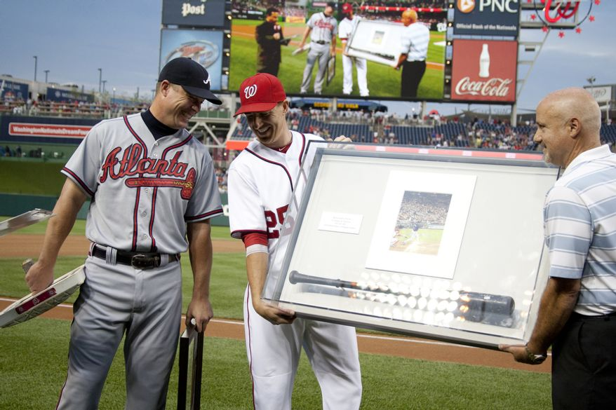 Washington Nationals Adam LaRoche, presents the bat that Chipper Jones hit the first home run with in Nationals Ball Park, with General Manager Mike Rizzo Wednesday, Aug. 22, 2012, in Washington, DC. Jones said he would be retiring after this session. He has played his entire 19 year career was an Atlanta Brave, winning one World Series title with them in 1995.  (Craig Bisacre/The Washington Times)