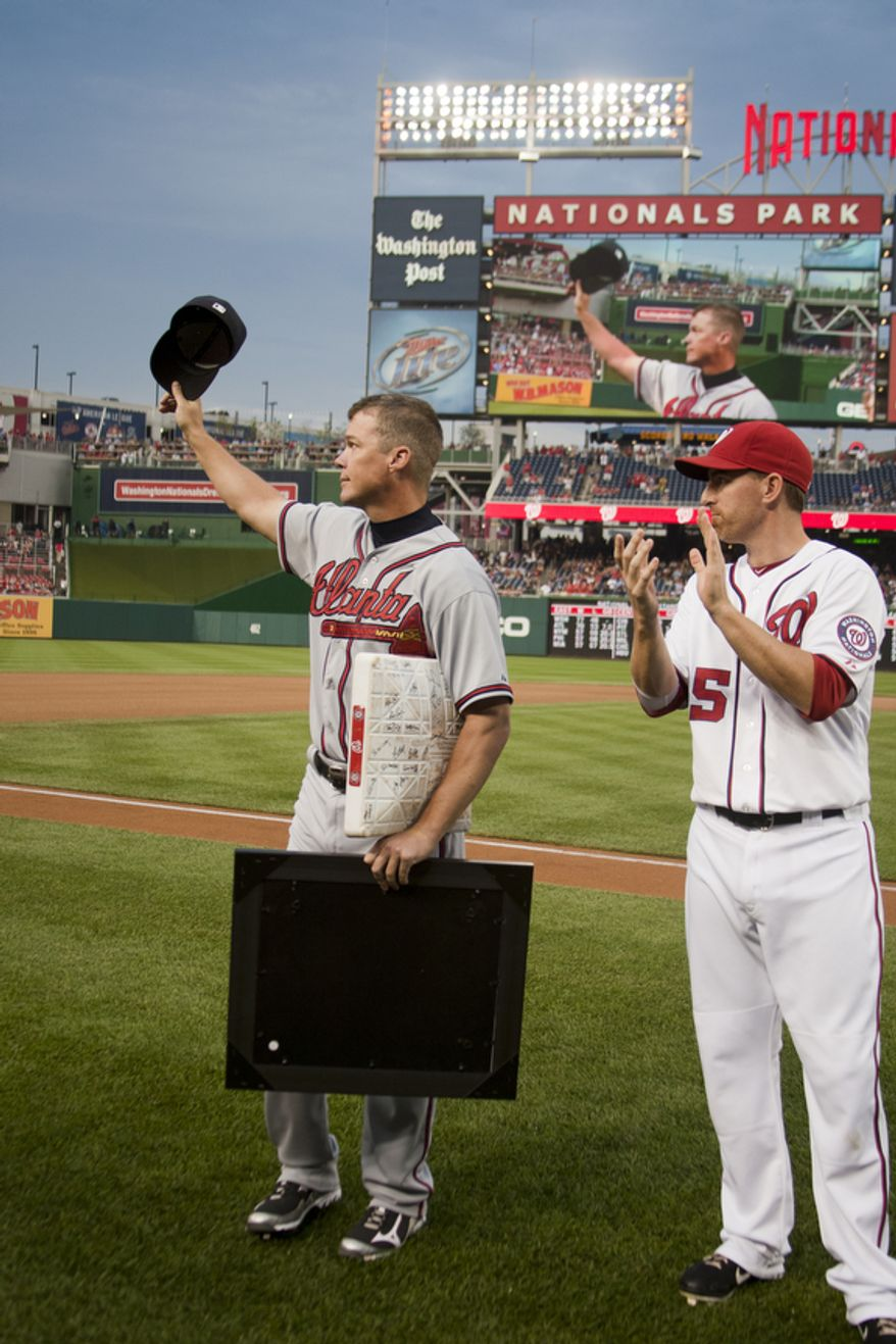 Chipper Jones waves to the crowd after a ceremony before the first pitch to honor veteran third baseman Chipper Jones, Wednesday, Aug. 22, 2012, in Washington, DC. Washington National Adam LaRoche looks on. (Craig Bisacre/The Washington Times)