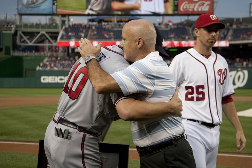 General Manager Mike Rizzo hugs Chipper Jones during a Washington Nationals ceremony before the first pitch to honor veteran third baseman Chipper Jones, Wednesday, Aug. 22, 2012, in Washington, DC. Jones has played his entire 19 year career was an Atlanta Brave, winning one World Series title with them in 1995.  (Craig Bisacre/The Washington Times)