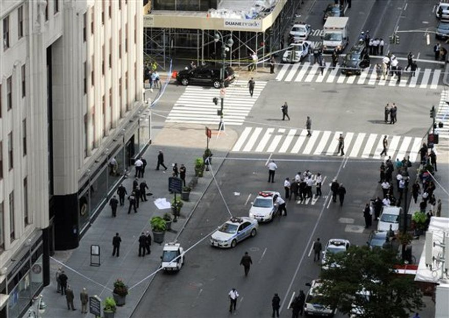 Police surround a sheet covered body, lower left, on a Fifth Avenue sidewalk as they investigate a multiple shooting outside the Empire State Building, Friday, Aug. 24, 2012, in New York. At least four people were shot on Friday morning and the gunman was dead, New York City officials said. A witness said the gunman was firing indiscriminately. Police said as many as 10 people were injured, but it is unclear how many were hit by bullets. A law enforcement official said the shooting was related to a workplace dispute. The official spoke on condition of anonymity because the investigation was ongoing. (AP Photo/ Louis Lanzano)