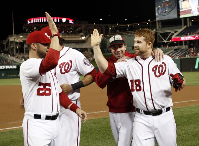 Washington Nationals' Chad Tracy, right, celebrates with Jesus Flores (26) and Sean Burnett, second from right, after Tracy reached first on a error scoring the winning run after a baseball game with the Atlanta Braves at Nationals Park on Tuesday, Aug. 21, 2012, in Washington. The Nationals won 5-4 in 13 innings. (AP Photo/Alex Brandon)
