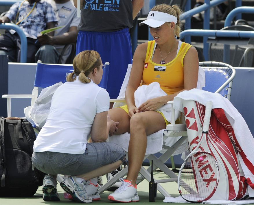 Caroline Wozniacki, of Denmark, speaks with trainer Kerri Whitehead before retiring from her semifinal match after losing the first set 7-5 against Maria Kirilenko, of Russia, at the New Haven Open tennis tournament in New Haven, Conn., on Friday, Aug. 24, 2012. A right knee injury suffered in the quarterfinals forced the retirement. (AP Photo/Fred Beckham)