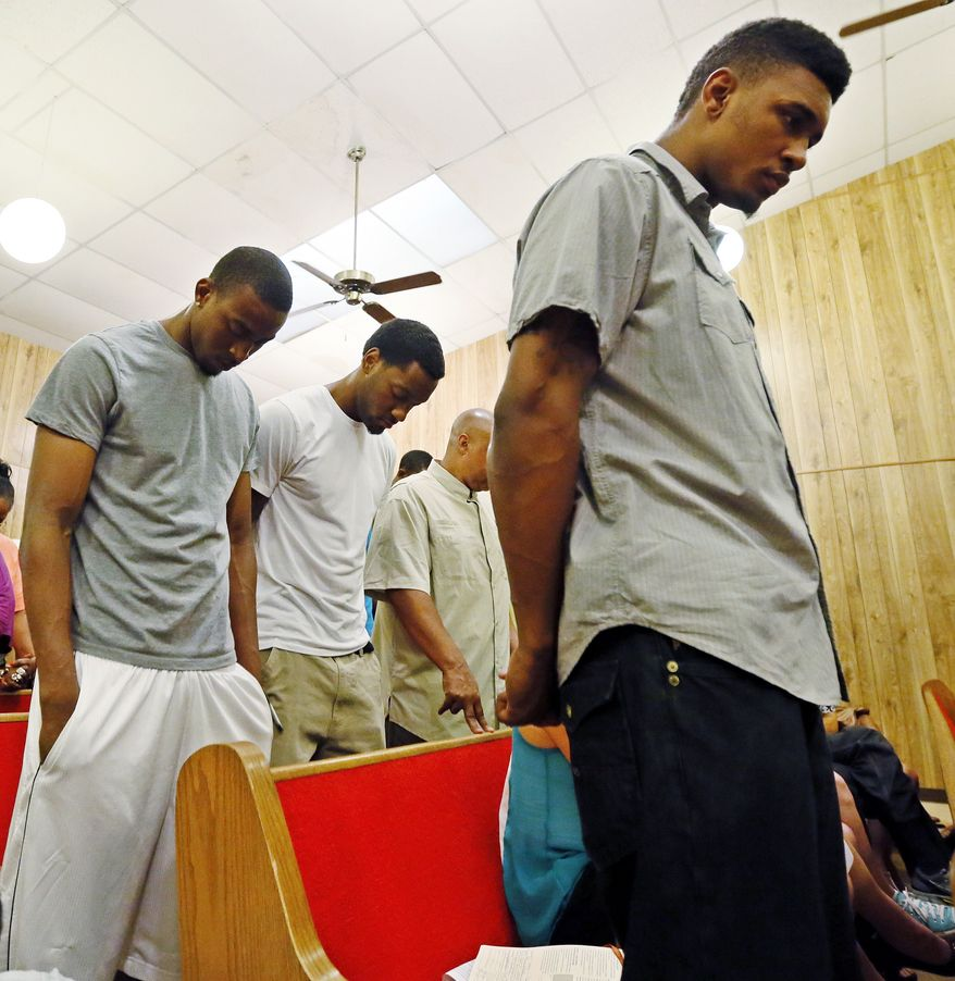 Oklahoma State basketball players Le'Bryan Nash, right, Markel Brown, left, and Brian Williams, center, bow their heads in prayer during a rally for their former teammate Darrell Williams, who was convicted last month of groping two women and reaching inside their pants without their consent at a house party, at Mt. Zion Baptist Church in Stillwater, Okla., Thursday, Aug. 23, 2012. Darrell Williams will be sentenced Friday for rape by instrumentation. (AP Photo/The Oklahoman, Nate Billings) TABLOIDS OUT