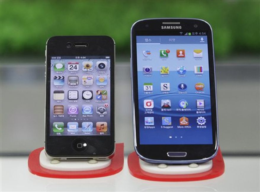 Samsung Electronics' Galaxy S III, right, and Apple's iPhone 4S are displayed at a mobile phone shop in Seoul, South Korea, Friday, Aug. 24, 2012. (AP Photo/Ahn Young-joon)