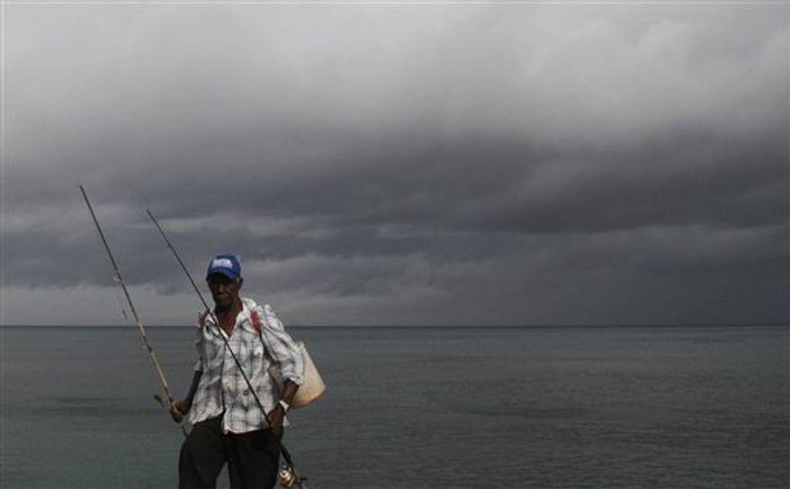 A fisherman walks home under cloudy skies along the shores of Santo Domingo, Dominican Republic, Thursday, Aug. 23, 2012. (AP Photo/Manuel Diaz)