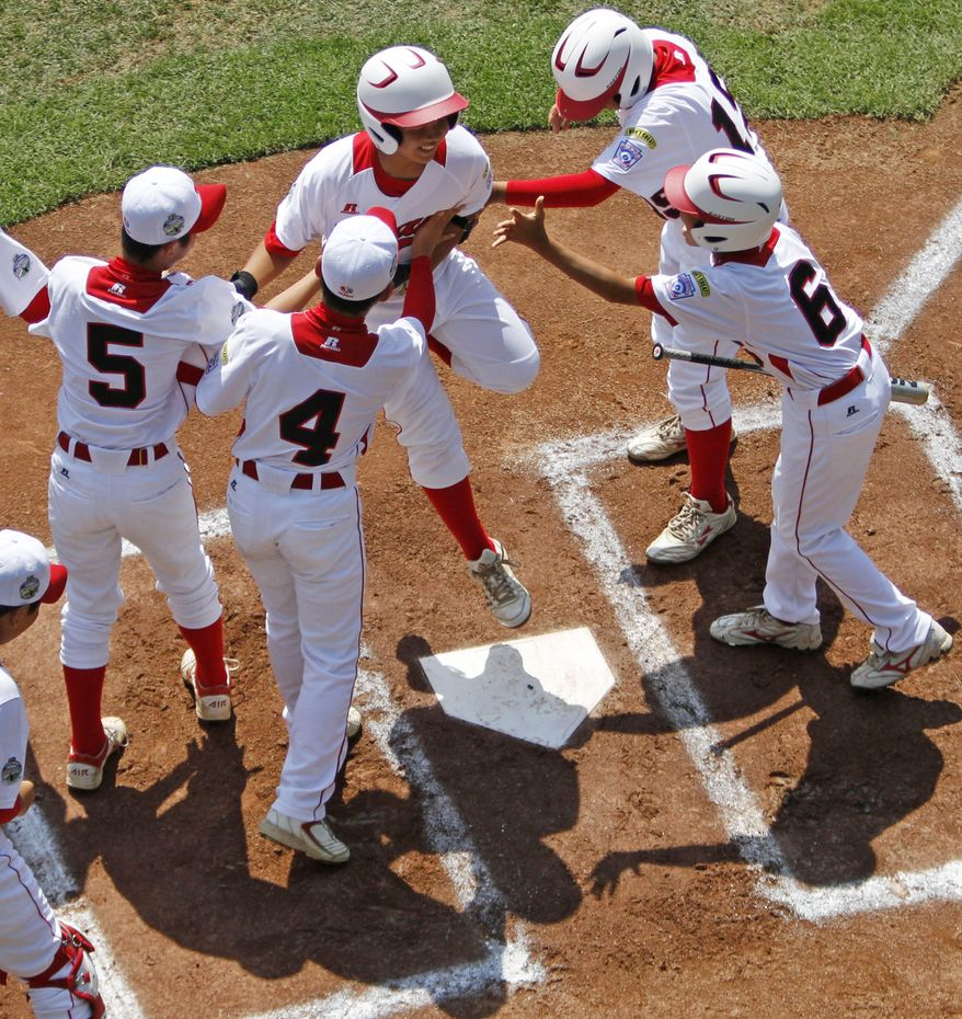 Tokyo's Satoru Aoyama leaps on home plate and celebrates with teammates after hitting a solo home run off Aguadulce, Panama, pitcher James Gonzalez in the first inning of the international championship baseball game at the Little League World Series, Saturday, Aug. 25, 2012, in South Williamsport, Pa. Tokyo won 10-2. (AP Photo/Gene J. Puskar)