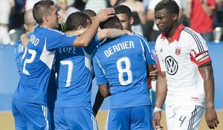 D.C. United's Brandon McDonald, right, walks by as players from the Montreal Impact celebrate after Patrice Bernier scored during second half MLS soccer action in Montreal, Saturday, Aug. 25, 2012.  (AP Photo/The Canadian Press, Graham Hughes)