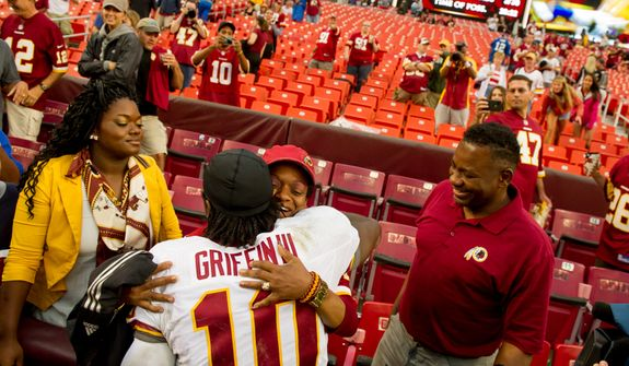 Washington Redskins quarterback Robert Griffin III (10) greets his family after the game at, Landover, Md., Saturday, August 25, 2012. (Andrew Harnik/The Washington Times)