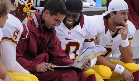 Washington Redskins quarterback Robert Griffin III (10) talks with Offensive Coordinator Kyle Shanahan late in the second quarter at FedEx Field, Landover, Md. Aug. 25, 2012. (Preston Keres/Special to The Washington Times)