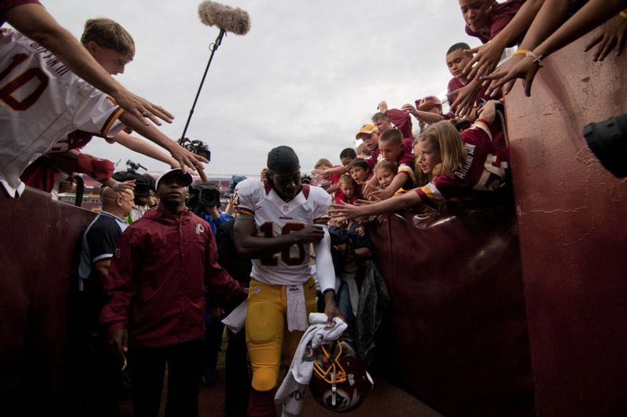 Fans try to touch Washington Redskins quarterback Robert Griffin III (10) as he leaves the field at the end of the Indianapolis Colts at Washington Redskins preseason football game, Saturday, August 25, 2012 in Washington, DC. Redskins won 30 - 17. (Craig Bisacre/The Washington Times)