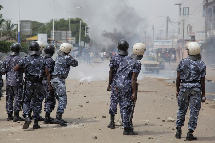 ** FILE ** Togolese security forces fire tear gas as they attempt to disperse thousands of angry opposition protesters and anti-government militants on the first day of a planned three-day rally in central Lome, Togo, on Tuesday, Aug. 21, 2012. The demonstrators set fire to tires, threw rocks and erected street barricades as they rallied to protest new electoral rules, perceived to favor the ruling party. (AP Photo/Erick Kaglan)