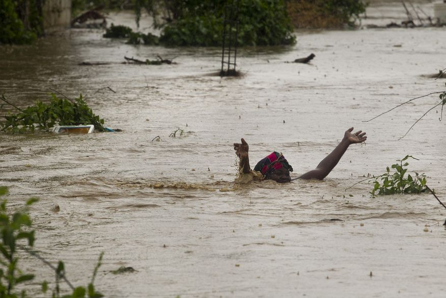 In this photo released by MINUSTAH, the U.N. mission in Haiti, a woman swims through floodwaters in a low-lying area affected by Tropical Storm Isaac in Port-au-Prince, Haiti, on Saturday, Aug. 25, 2012. (AP Photo/MINUSTAH, Logan Abassi)
