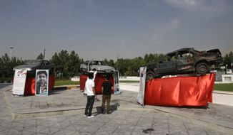 Three cars that were hit by bombs as they carried Iranian scientists are displayed outside a conference hall hosting the meeting of the Non-Aligned Movement in Tehran on Sunday, Aug. 26, 2012. (AP Photo/Vahid Salemi)