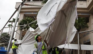 Joel Jimenez (right) and Issac Page remove an awning outside the Tampa Convention Center, which will serve as the media center for the Republican National Convention, in Tampa, Fla., on Sunday, Aug. 26, 2012. Precautions were being taken in anticipation of Tropical Storm Isaac. (AP Photo/Lynne Sladky)