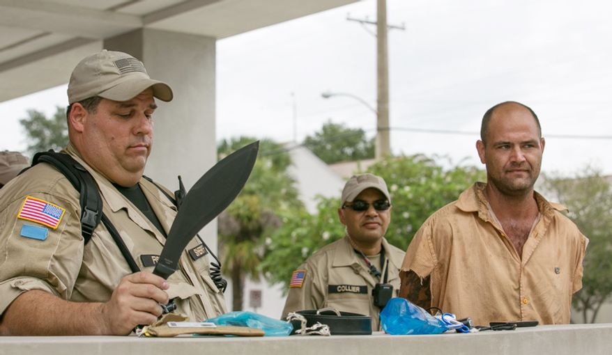 Officer Fisher holds a 9 inch KA-BAR knife that was confiscated from Jason Wilson, right, during a protest, in Tampa, Fla., Sunday, August 26, 2012. Police arrested Jason Wilson when they noticed he was carrying the knife. (Andrew S. Geraci/The Washington Times)