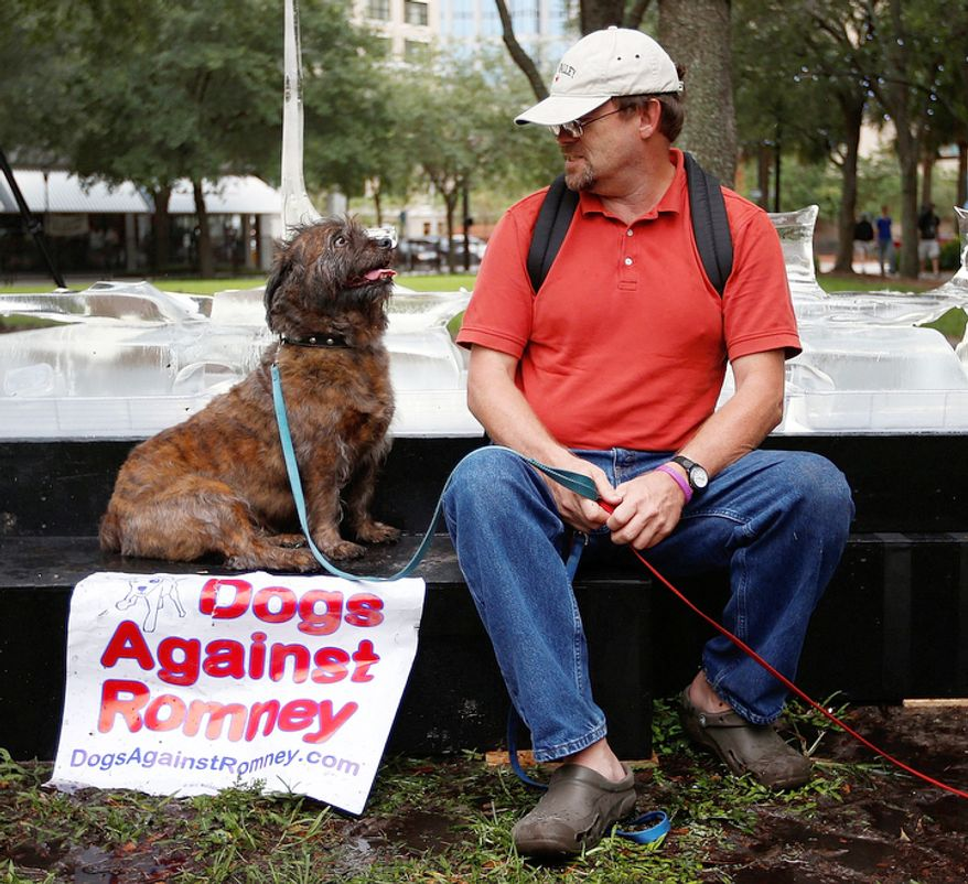 Robert Berg of Sarasota, Fla. looks at his dog during a Dogs Against Romney protest before the Republican National Convention in Tampa, Fla.  (AP Photo/Jae C. Hong)
