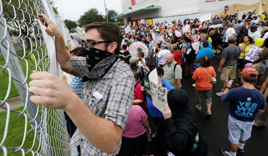 Demonstrators chant and walk and climb  a fence near Tropicana Field during a protest march, Sunday, Aug. 26, 2012, in St Petersburg, Fla. Hundreds of protestors gathered a park in downtown St. Petersburg to march in demonstration against the Republican National Convention. (AP Photo/Patrick Semansky)
