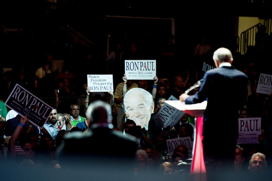Supporters hold up a large image of Ron Paul as he speaks.   (Andrew Harnik/The Washington Times)