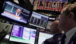 Specialists watch from the New York Stock Exchange in September 2011 as President Obama makes a speech. The S&P 500 and Nasdaq stock indexes have both fared better in Mr. Obama's first term than in those of five previous presidents. (Associated Press)