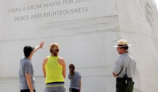 """Ben Heller of Bloomfield Hills, Mich, with his wife Gabby and their daughter Zoe, 13, speak with Park Ranger Eric Pominville on Monday about the quote on the Martin Luther King Jr. Memorial on the Mall. """"I think if you're going to quote somebody, you should quote them properly,"""" Mr. Heller said about the paraphrased line. """"It is etched in stone, but it can be fixed?"""" (Eva Russo/Special to The Washington Times)"""