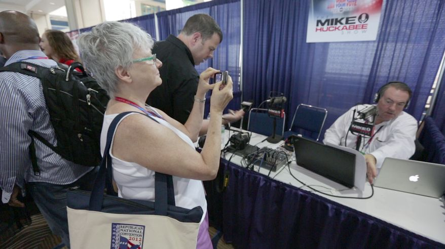 A guest attending the National Republican Convention (RNC), snaps a quick photo of former 2008 presidential candidate Mike Huckabee during his radio show at the convention center, in Tampa, FL., Monday, August 27, 2012. The RNC will run from the 27th through the 30th of August.(Andrew S. Geraci/The Washington Times)