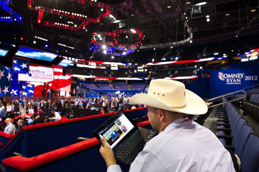 Toby Olin, of New Salem, N.D. watches a Ron Paul speech on his laptop near the Republican National Convention floor after Chairman of the Republican National Committee Reince Priebus calls a recess on the first day of events.   (Andrew Harnik/The Washington Times)