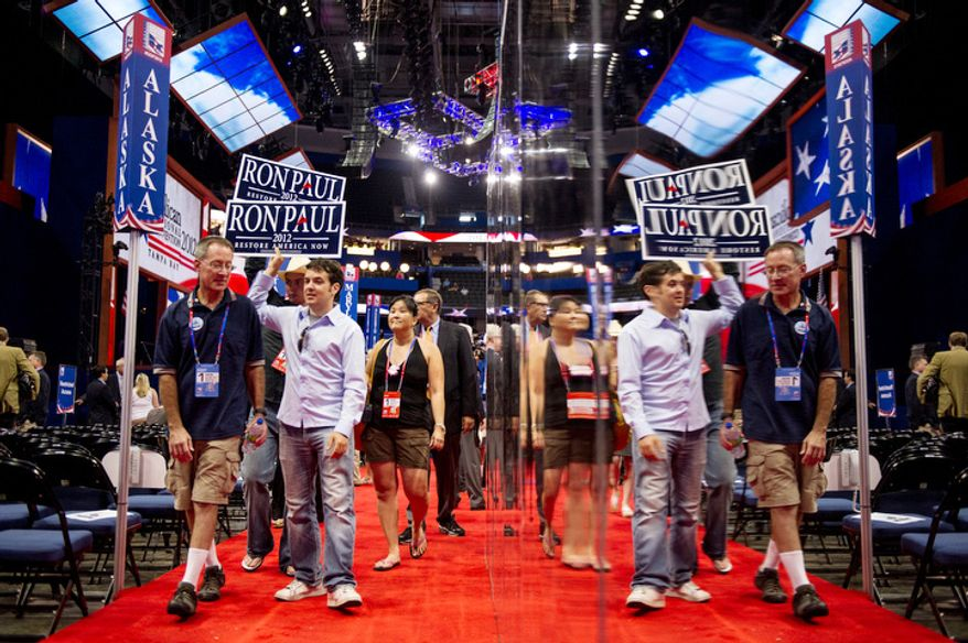 Ron Paul supporters walk the Republican National Convention floor after Chairman of the Republican National Committee Reince Priebus calls a recess on the first day of events because of Hurricane Isaac.   (Andrew Harnik/The Washington Times)