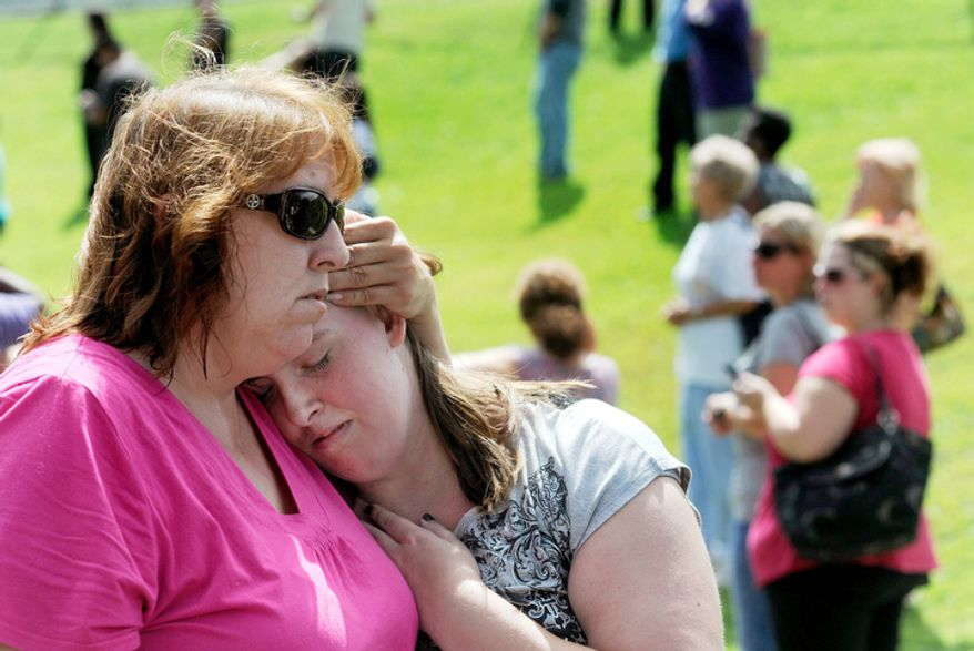 Tracie Bradford, of Perry Hall, Md., consoles her daughter Leah, a student at Perry Hall High School who says she was in the school's cafeteria when a student was shot there and critically wounded on the first day of classes. (AP Photo/Steve Ruark)