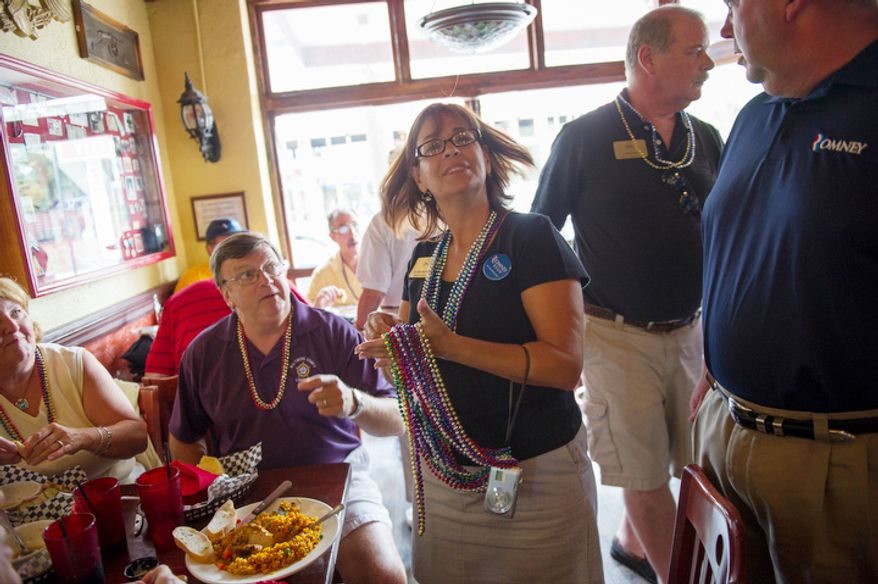 Alternate delegate from Baltimore County, Maryland Gloria Murphy passes out Mardi Gras style beads to fellow to people as she and other delegates from Maryland take shelter from the spotty rain at Gaspar's Grotto as tropical storm Isaac delays the kickoff of Republican National Convention. (Rod Lamkey Jr./The Washington Times)