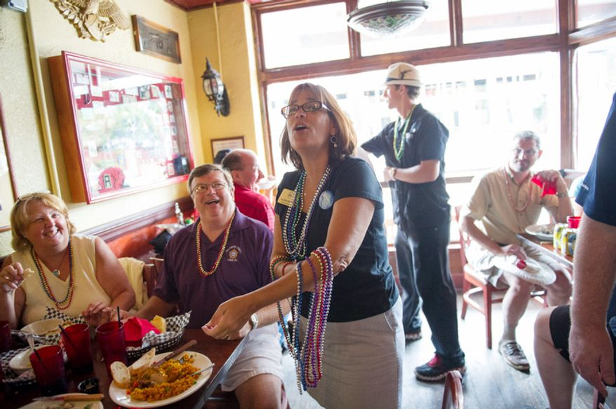 Alternate delegate from Baltimore County, Maryland Gloria Murphy passes out Mardi Gras style beads as she and other delegates from Maryland take shelter from the spotty rain at Gaspar's Grotto. (Rod Lamkey Jr./The Washington Times)