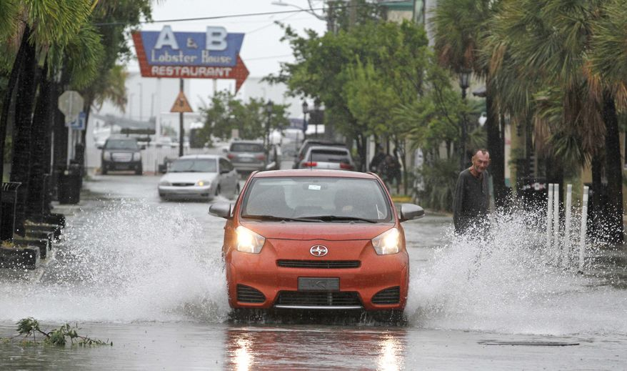 A car goes through high water from heavy rains associated with Tropical Storm Isaac in Key West, Fla., on Sunday, Aug. 26, 2012. (AP Photo/Alan Diaz)