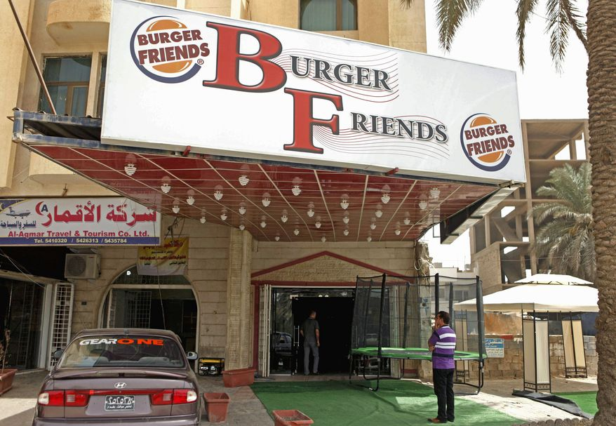 A customer stands outside Burger Friends restaurant. An Iraqi doctor said he fears the popularity of American-style food will make children fatter. Iraqi entrepreneurs and foreign investors are driving the food craze. (Associated Press)
