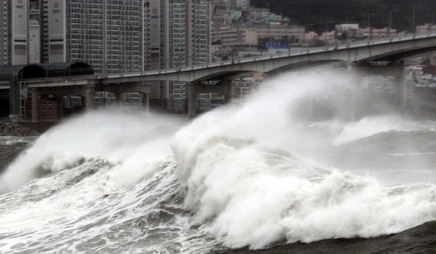 A wave breaks along a bridge off the southern port city of Busan, South Korea, as Typhoon Bolaven brings heavy rain and wind. The typhoon killed nine, caused cancellation of joint U.S.-South Korean military exercises and cut off power to 1.7 million homes and businesses. (Associated Press)