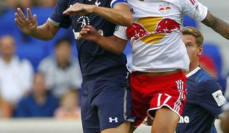 Tottenham Hotspur's Michael Dawson (20) battles New York Red Bulls' Tim Cahill (17) for a header in the first half during a friendly soccer match at Red Bull Arena in Harrison, N.J., Tuesday, July 31, 2012. (AP Photo/Rich Schultz)