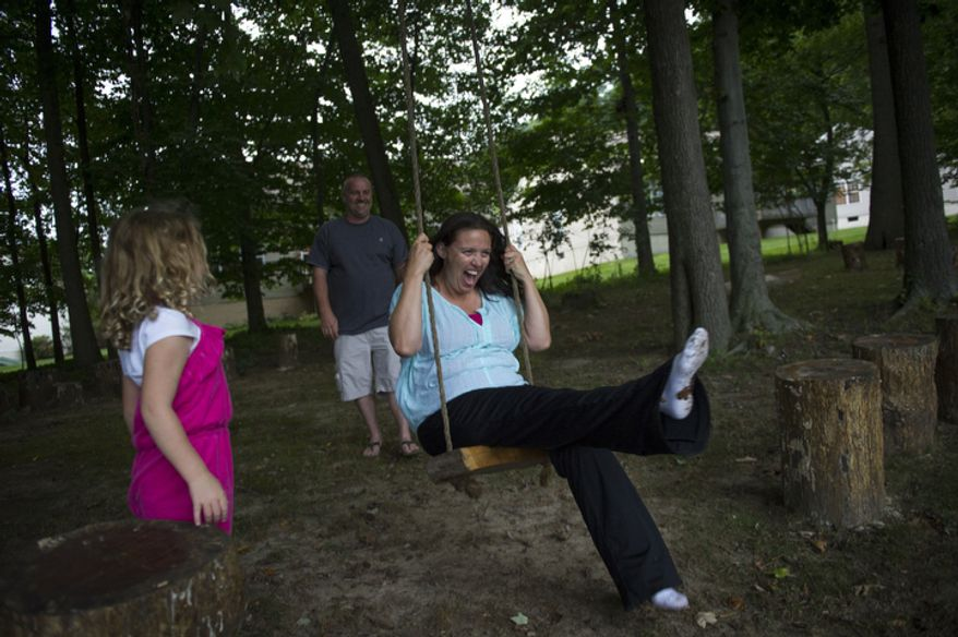 With their daughter Catalina, 5, looking on, Joe Carr pushes his wife Sofia on a swing in their backyard after sitting for a portrait at their home in Downingtown, Pa. (Rod Lamkey Jr./The Washington Times)